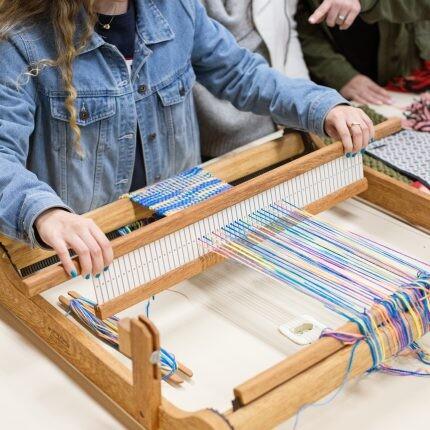 estudantes do curso de design de moda da pucpr em aula prática no tear