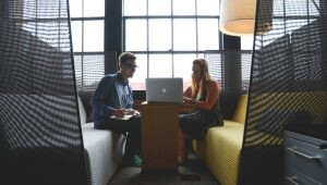 Dois jovens observam atentos a tela de um notebook. Eles estão sentados em bancos almofadados, um de frente para o outro.