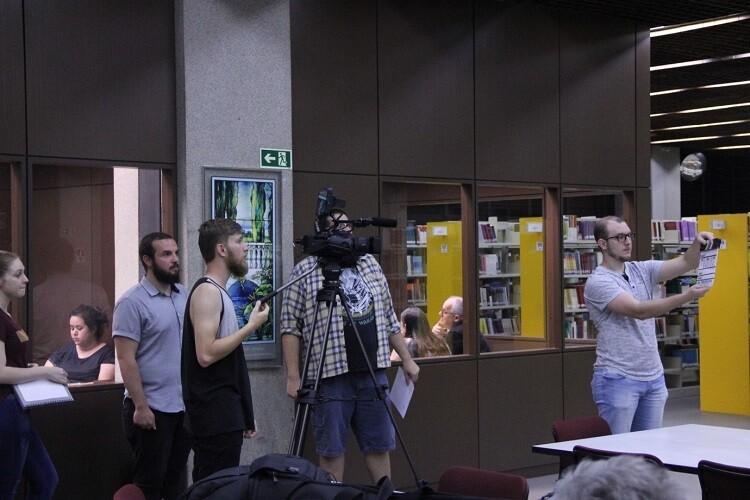 Cinco estudantes na Biblioteca da PUCPR gravando cena da série