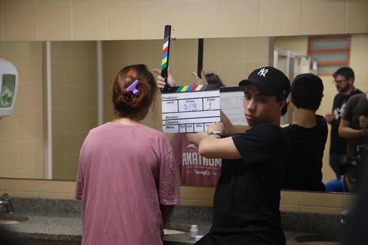 Estudantes durante garavação de cena em banheiro da PUCPR