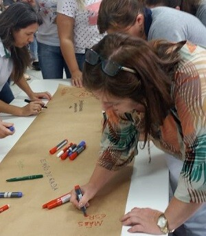 Sevidores públicos escrevendo em cartaz durante oficina