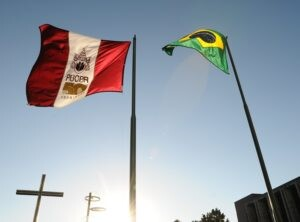 Bandeiras da PUCPR e do Brasil com cruz da capela ao fundo