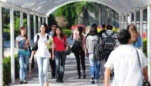 Estudantes da PUCPR andando nos corredores da Universidade