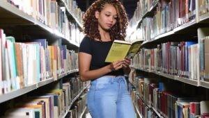 Estudante lendo em corredor da biblioteca